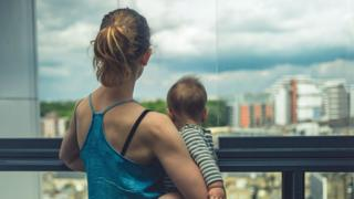 Mother and baby looking out of their apartment at city beyond