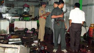 Police inspect the interior after the blast at Gokul Chat in Hyderabad