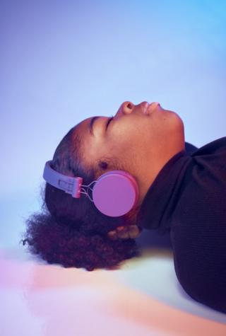 A portrait of a woman lying on the floor listening to headphones