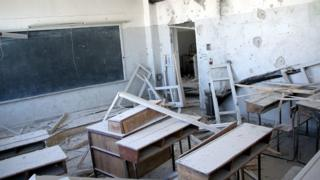 damaged desks in a classroom in a bombed Syrian school