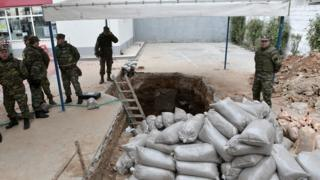 Greek Army officers conduct preparation work before they excavate an unexploded World War II bomb which was found at a gas station in Thessaloniki