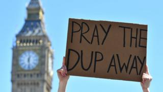 A protester holds up a placard as they protest in Parliament Square in front of the Houses of Parliament in central London on 10 June 2017 against the Democratic Unionist Party (DUP)