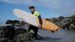 Ryan O'Carroll with surf board