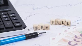 Dice with 'buy' and 'sell' written on them on a graph with euros, a calculator and pen