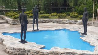 Three figures urinate in a pool shaped like Bosnia and Hercegovina