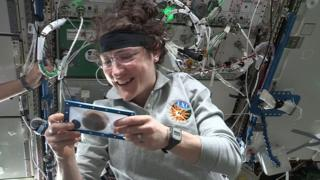 An astronaut holds a cookie on the International Space Station