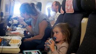항공기 좌석에 앉아 기내식을 먹고 있는 엄마와 아이