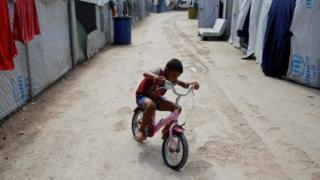 A boy rides a bicycle at the Souda camp for refugees and migrants, on the island of Chios (07 September 2016)