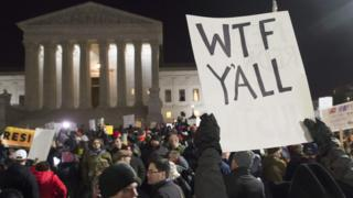 "The US Supreme Court, seen in the background, is obstructed by a protesters's sign reading ""WTF y'all"""