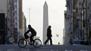 People cross an almost deserted avenue in Buenos Aires on July 10, 2009.
