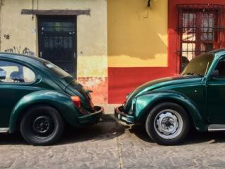 Two Volkswagen Beetles parked next to each other