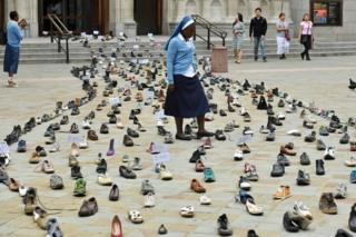 Catholic Agency For Overseas Development's (CAFOD) Sister Clara from Zambia, walks through shoes displayed outside Westminster Cathedral in central London on August 15, 2018.
