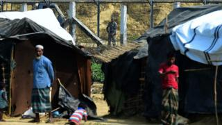 A Myanmar security personnel keeps watch along the Myanmar-Bangladesh border as Rohingya refugee stand outside their makeshifts shelters near Tombru