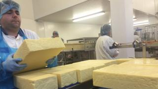A worker packs cheese on the production line