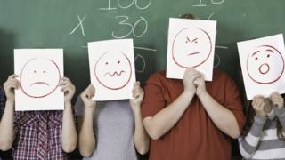 Crianças em frente a quadro negro segurando cartazes com caras tristes