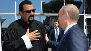 Russian President Vladimir Putin (right) speaks with US action movie actor Steven Seagal (left) at the Russia's first ever Eastern Economic Forum