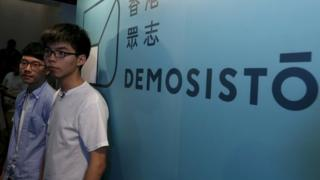 Student leader Joshua Wong (R) and Chairman Nathan Law pose in front of a backdrop during the launch ceremony of their new political party Demosisto in Hong Kong, 10 April 2016