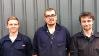 Thomas Allday, Dafydd Hughes and Sam Buffrey stand in a line on front of a corrugated wall in overalls