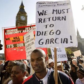 """Joven con un carteL que dice """"Debemos regresar a Diego Garcia"""""""