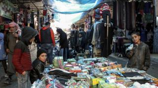 Syrians walk in a popular market in Manbij, northern Syria (31 December 2018)