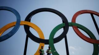 Brazilian badminton players Lohaynny Vicente (left), 20, and her sister Luana Vicente, 22, stand under a set of Olympic rings installed at Madureira Park in Rio de Janeiro (04 May 2016)