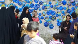Orang berjalan di depan keramik biru yang dipercaya bisa mengusir mata setan, atau oleh warga setempat disebut sebagai ibu dari tujuh mata, di Najaf, Irak, 10 Februari 2015.