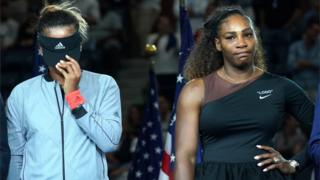 Naomi Osaka pulls her visor down covering her face, Serena Williams stands hand on one hip