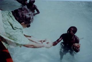 ที เอ็น พันดิต กำลังยื่นลูกมะพร้าวให้กับผู้ชายชนเผ่าเซนทิเนล