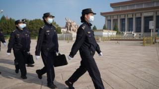 Police women wearing face masks walk in Tiananmen Square before the opening of the National People's Congress on May 22, 2020 in Beijing