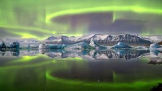 Aurora polar em um lago de uma geleira