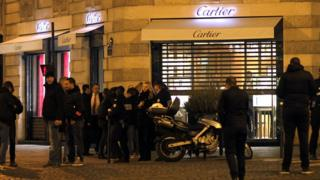 Police stand in front of a Cartier jewellery store on the Champs-Elysees avenue in Paris, after a robbery in November 2014
