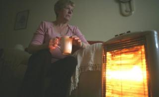 Woman sitting at heater
