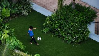 Child playing football in garden