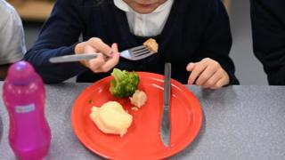 A school girl eating school dinner.