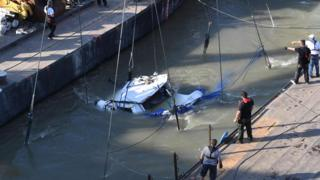 Rescue workers and crew members are helped by a giant floating crane, the Clark Adam ship, to lift the sunken sightseeing boat Mermaid in Budapest on June 11, 2019