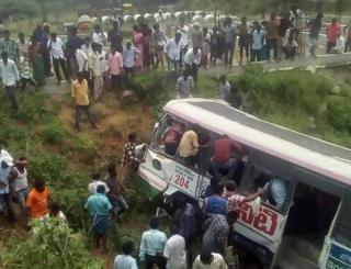 Onlookers and rescuers gather around the bus in Telangana state.