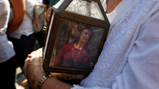 A woman holds a lantern with a picture of investigative journalist Daphne Caruana Galizia, who was assassinated in a car bomb attack, during a protest outside the law courts in Valletta, Malta, October 17 2017