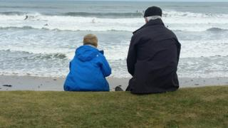 Boy and granddad watch dad surfing at St Andrews