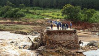 Timber company workers stand stranded on a damaged road on 18 March 2019, at Charter Estate in Chimanimani, eastern Zimbabwe.