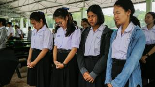 Classmates of the Wild Boars soccer team pray at the Maisai Prasitsart school before classes the morning as the third rescue mission to free the last four boys and their coach from a flooded cave is under way