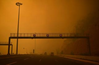 A road block is set up amid smoke as a wildfire burns in Kineta, near Athens, on July 23, 2018