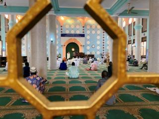 Worshippers sit inside and pray.