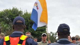 South Africans supporting the white supremacist Afrikaner Resistance Movement (AWB) fly the apartheid-era flag on April 6, 2010 outside a South African court in the north-western town of Ventersdorp, where hundreds demonstrated ahead of the appearance of two men accused of the April 4 killing of far-right leader Eugene Terre'Blanche.