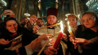 Ukrainians light candles with the Holy Fire during an Orthodox Easter Mass at St Volodymir Cathedral in Kiev