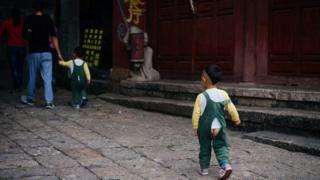 Niño en la calle usando un pantalón abierto.