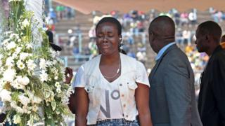 A woman weeps at the public viewing of the body of late former Zimbabwean president Robert Mugabe in the coffin as it is lying in state in Harare, Zimbabwe, 13 September 2019.