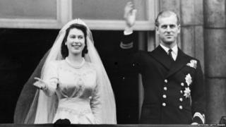 Princess Elizabeth and Prince Philip on their wedding day waving from a balcony