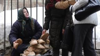 An elderly street vendor sitting in snowy weather while two passing pedestrians examine her woven straw shoes (2010 file photo)