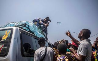A man, standing on top of a car, throws a bottle of water to another man