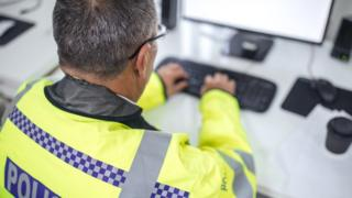 Police officer inputting data